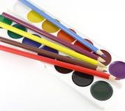 Color pencils and colours palette. Color pencils lying on the colours palette on white Stock Photos