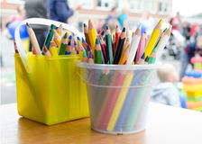 Color pencils or crayons. Colorful pencils or crayons in plastic containers on table outside on a school yard Royalty Free Stock Images