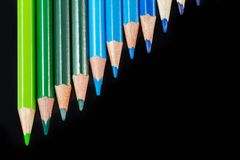 Color pencils in diagonal formation isolated on black cool palet Royalty Free Stock Photography