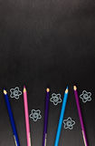 Color pencils and different paper clips on dark background. Stock Image