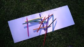 Color pencils falling on white paper stock footage