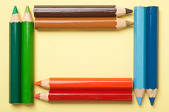 Color pencils forming a rectangle frame. Colorful color pencils forming a rectangle frame on a piece of yellow paper Royalty Free Stock Image