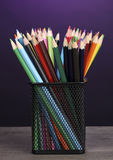 Color pencils in glass on wooden table Royalty Free Stock Images