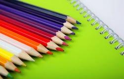 Color pencils on green notebook. Closeup of color pencils on green notebook Royalty Free Stock Photo