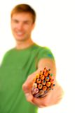 Color pencils in  hand. Guy suggests and holds  set of color pencils in  hand on  white background Stock Photo