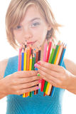 Color pencils in hands. Color rainbow pencils and teenager hands with multicoloured nails Royalty Free Stock Image