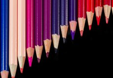 Color pencils in diagonal formation isolated on black warm palet Stock Image