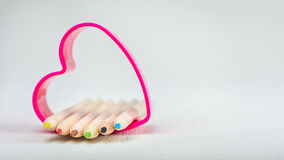 Color pencils laying in red heart symbol and represent love to creativity drawing.  royalty free stock photography