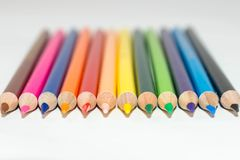 Colorful close up tips of color pencils aligned and pointing forward royalty free stock photography