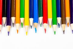 Color pencils lined up in a row against a white background royalty free stock photos