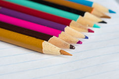 The color pencils lying on an open writing-book. Close up Stock Images