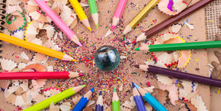 Color Pencils and a marble on pencil shavings. Color Pencils and a marble on some pencil shavings Royalty Free Stock Images