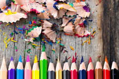 Color pencils. Multi color pencils and particle on wooden table, selective focus Royalty Free Stock Photography