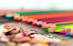 Color pencils. Multi color pencils and particle on wooden table, selective focus Stock Photos
