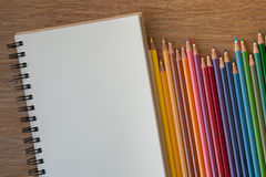 Color pencils with notebook. On wooden table Royalty Free Stock Images