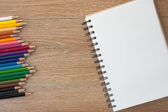Color pencils with notebook. On wooden table Royalty Free Stock Photos