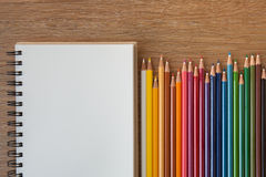 Color pencils with notebook. On wooden table Royalty Free Stock Photo