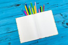 Color pencils and notepad. school concept. The top view of color pencils and notepad on blue wooden background. School concept Royalty Free Stock Photos