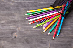Color pencils and office bin on wooden background Royalty Free Stock Photo