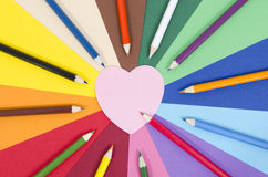 Color pencils on paper with pink heart memo note. Royalty Free Stock Photo