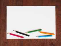Color pencils and a paper on wooden background Stock Photography