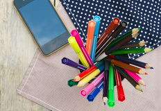 Color pencils and pen on wooden table see on top view. Royalty Free Stock Photos