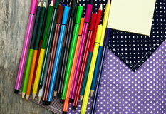 Color pencils and pen on wooden table see on top view. Royalty Free Stock Image