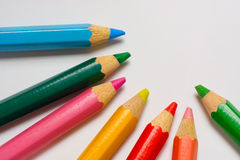 Color pencils on a piece of white paper. Closeup of some color pencils on a piece of white paper Stock Image