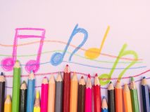 Color pencils place on white paper background with Music note drawing. Education concept. Color pencils place on white paper background with Music note drawing royalty free stock image