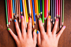 Color pencils. Color rainbow pencils and teenager's hands with multicoloured nails Royalty Free Stock Photos