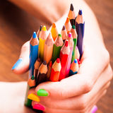 Color pencils. Color rainbow pencils in teenager's hands with multicoloured nails Stock Photography