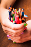 Color pencils. Color rainbow pencils in teenager's hands with multicoloured nails Stock Images