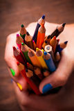 Color pencils. Color rainbow pencils in teenager's hands with multicoloured nails Royalty Free Stock Photo