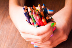 Color pencils. Color rainbow pencils in teenager's hands with multicoloured nails Royalty Free Stock Images