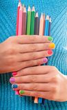Color pencils. Color rainbow pencils and teenager's hands with multicoloured nails Royalty Free Stock Images