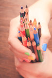 The Color pencils. Color rainbow pencils in teenager's hands with multicoloured nails Royalty Free Stock Image