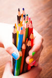 The Color pencils. Color rainbow pencils in teenager's hands with multicoloured nails Stock Photos