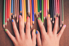 The Color pencils. Color rainbow pencils in teenager's hands with multicoloured nails Royalty Free Stock Images
