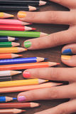 The Color pencils. Color rainbow pencils in teenager's hands with multicoloured nails Stock Photo