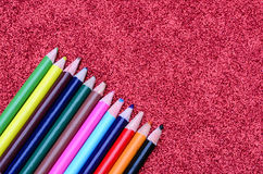 Color pencils on red glitter paper Stock Image