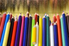 Color pencils with reflection. Pencils of multiple colors laying inside a tin box reflected in the side of the box Royalty Free Stock Image