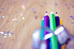 Color pencils with ribbon and confetti bokeh Royalty Free Stock Photos