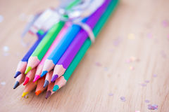 Color pencils with ribbon and confetti bokeh Royalty Free Stock Image