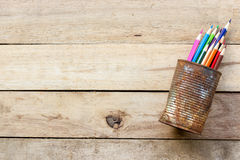Color pencils in rusty tin can. Wood table Stock Photos