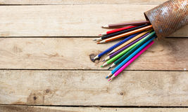 Color pencils in rusty tin can. Wood table Stock Images