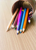 Color pencils in rusty tin can. Wood table Royalty Free Stock Image