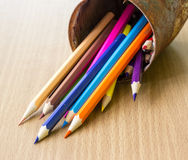 Color pencils in rusty tin can. Wood table Stock Photo