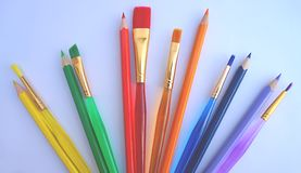 Color pencils and same color paint brushes, stuff for new primary school year activities stock images