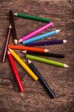 Color pencils scattered on wood background. Color pencils on wood background stock image