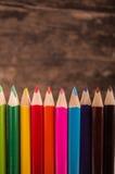 Color pencils scattered on wood background. Color pencils on wood background royalty free stock photo